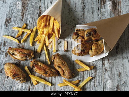 roasted chicken wings with fries from above - Stock Photo