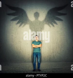 Casual confident man arms crossed. Full length portrait casting a superhero shadow with angel wings on a dark room wall. Inner power, ambition and lea - Stock Photo
