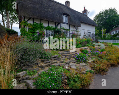 Typical Hampshire country cottage - half timbered and thatched - with pretty front garden in the village of Easton near Winchester in the South Downs  - Stock Photo