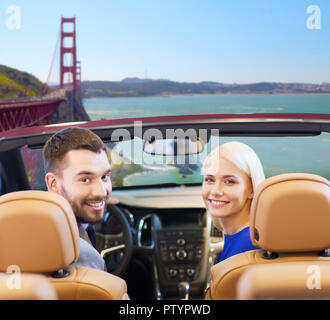 couple driving in convertible car and looking back - Stock Photo