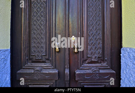 The proud front door of a home in Arganil, Central Portugal, displaying two brass hand door knockers and ornate carved wooden doors. - Stock Photo