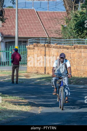 Johannesburg, South Africa - unidentified black men walking and cycling to their jobs through the streets of a residential suburb image has copy space - Stock Photo