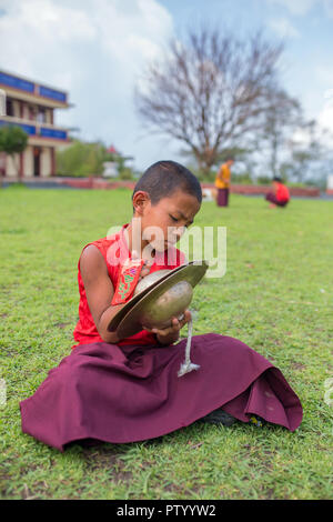 Gangtok, India - May 3, 2017: Unidentified young novice buddhist monk in traditional red robes practicing in playing Tibetan music instrument tingsha  - Stock Photo