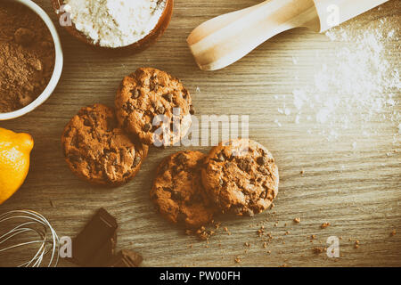 Homemade cookies with chocolate chips on wooden table with ingredients in a rustic kitchen vintage. Horizontal composition. Top view - Stock Photo