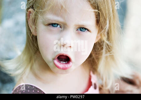 Cute blond child angry and throwing a temper tantrum - Stock Photo