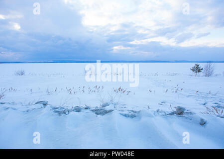 beautiful sunset over the lake covered with ice in winter - Stock Photo