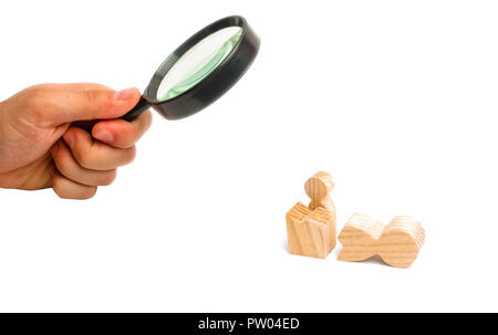 Magnifying glass is looking at a small figure of a man looks out of the remains of a large figure. a way out of the comfort zone. Reincarnation into a