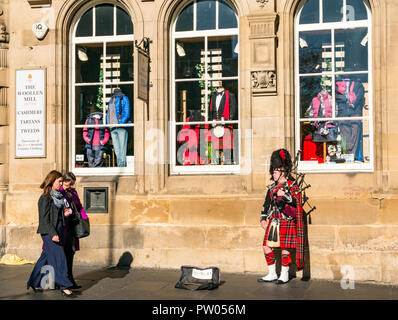Women walking past street busker dressed in Scottish military uniform with kilt, bearskin hat and bagpipes, Royal Mile, Edinburgh, Scotland, UK - Stock Photo