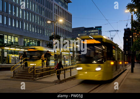 Two Metrolink trams leave St Peter's square stop at night in Manchester City Centre, UK. - Stock Photo