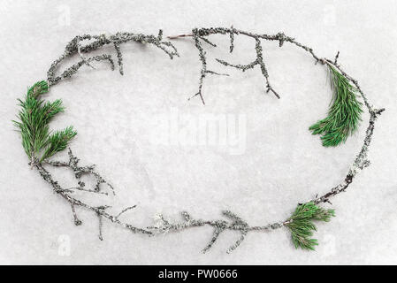 Frame made of mossy twigs and green pine branches, on concrete background. Nordic nature. - Stock Photo