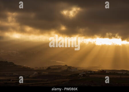 Early morning sun rays breaking through a gap in the clouds lighting up the hillside villages in the municipility of Guia de Isora, Tenerife, Canary I - Stock Photo