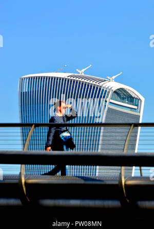 Man (out of focus) walking across the Millennium Bridge with the Walkie Talkie Building (20 Fenchurch Street) in focus behind, London, England, UK. - Stock Photo