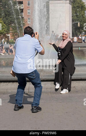 An Islamic woman in a hijab poses for a photo near the fountain in Washington Square Park in Manhattan, New York City. - Stock Photo