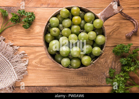 View from above on ripe green variety of small round cherry tomatoes in round natural  bowl on textured wooden table surface with green parsley leaves - Stock Photo
