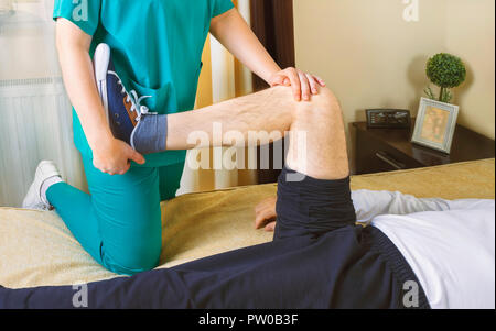 Physiotherapist doing exercises for leg recovery to immobilized male patient at home. People, health and recovery concept. Stock Photo
