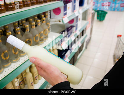 the buyer selects the alcoholic beverage holding a man's hand in the store. - Stock Photo