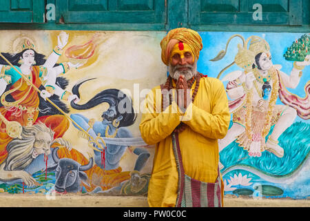 A Sadhu or holy man at Pashupatinath Temple, by the Bagmati River, Kathmandu, Nepal, with folded hands for the traditional Hindu greeting of Namaste - Stock Photo