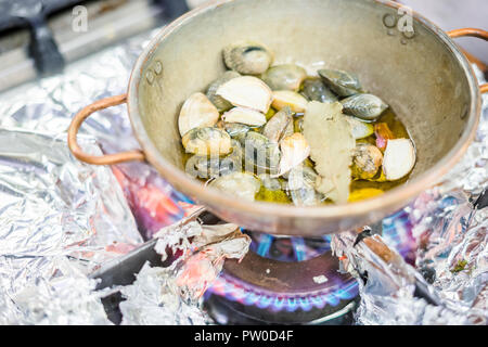 Portion of clams with bay leaves and garlic in a copper pot on gas stove - Stock Photo