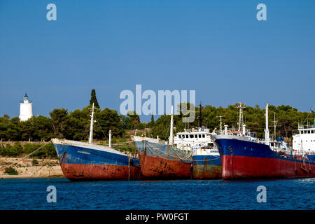 Abandoned boats moored in Spetses old harbour near the lighthouse, Greece. - Stock Photo