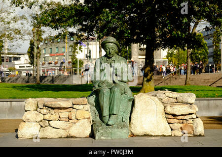 A bronze copy of a statue of the Irish writer Pádraic Ó Conaire seated in Eyre Square Galway. The original statue is now in the Galway City museum. - Stock Photo
