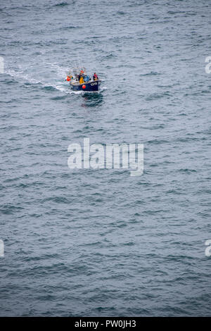 Two fishermen in a boat on the sea returning to Boscastle harbour in Cornwall, England, UK - Stock Photo