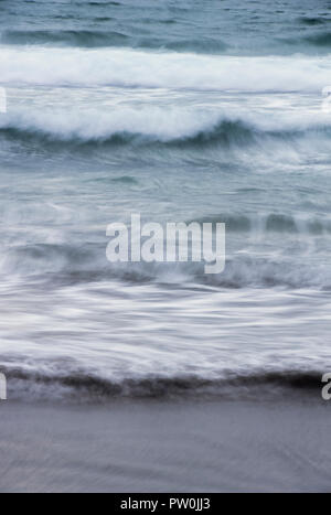Long exposure of waves and the incoming tide splashing onto a sandy beach - Stock Photo