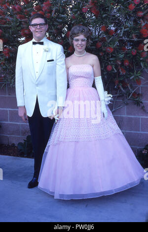 1962, America, going to the prom.....a young man wearing a white tuxedo and and a young woman wearing a long frilly pink dress stand together for a picture before they attend the prom, a traditional and important end of term dance and social event for US high school students. In the 50s and 60s, the prom was more of a couple's event, where a boy would ask a girl to be his date and would escort her after picking her up at her home and having lots of picture taken! - Stock Photo