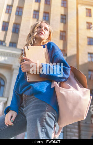 Student with notebooks at the university - Stock Photo