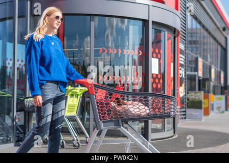 woman with trolley at the supermarket door - Stock Photo