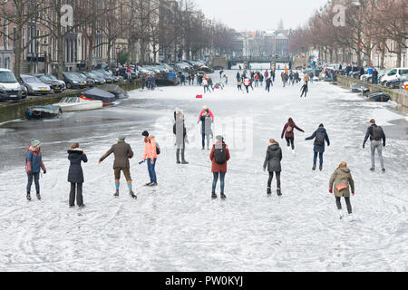 Ice on canal Keizersgracht, Amsterdam and ice skating people. A typical Dutch winter scene. - Stock Photo