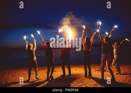 Group of happy friends is having fun or celebrating something with signal fires at evening beach - Stock Photo
