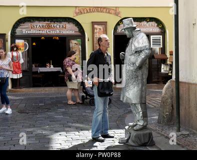 Mime artist talking to a man in Prague Czech Republic - Stock Photo