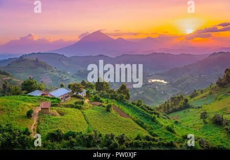 Kisoro Uganda beautiful sunset over mountains and hills of pastures and farms in villages of Uganda. Amazing colorful sky and incredible landscape to - Stock Photo