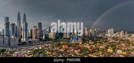 Panoramic view of city skyline with rainbow, Kuala Lumpur, Malaysia - Stock Photo