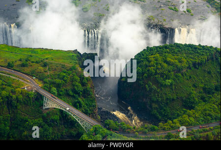 Victoria Falls in Zimbabwe and Zambia, Aerial helicopter photo, green forest around amazing majestic waterfalls of Africa. Livingston Bridge above the - Stock Photo