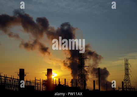 the sun rises over the coal power station on a bitterly cold morning. - Stock Photo