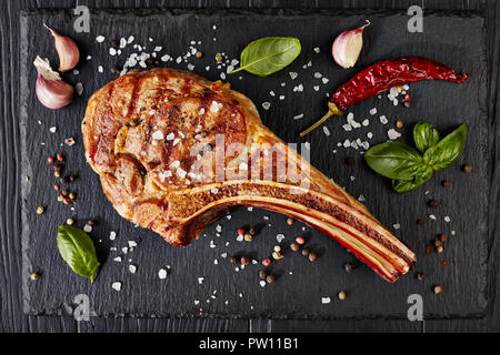close-up of grilled tomahawk steak or cowboy beef steak on a black slate board with garlic, fresh basil, view from above, flat lay - Stock Photo