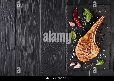 roasted tomahawk steak or cowboy beef steak on a black slate board with garlic, fresh basil, view from above, flat lay - Stock Photo