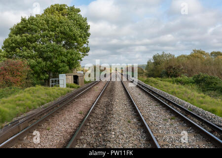 railway lines or rail train tracks tapering into the distance to a vanishing or disappearing point in the countryside. - Stock Photo