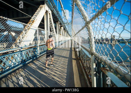 NEW YORK CITY - CIRCA AUGUST 2018: A young man jogs across the Manhattan Bridge on the pedestrian walkway with a sunset view of the Brooklyn Bridge. - Stock Photo