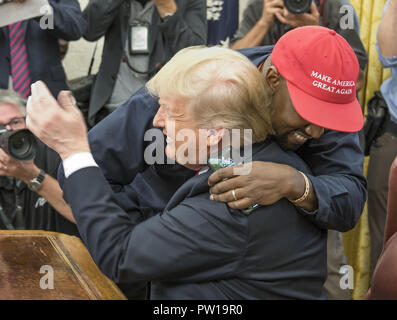Washington, District of Columbia, USA. 11th Oct, 2018. KANYE WEST hugs United States President DONALD J. TRUMP hugs they meet with Jim Brown in the Oval Office of the White House. Credit: Ron Sachs/CNP/ZUMA Wire/Alamy Live News - Stock Photo