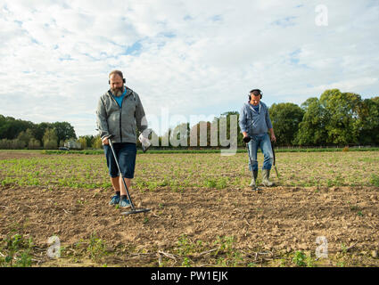 12 October 2018, North Rhine-Westphalia, Moenchengladbach: Marcel Spreyer (L) and Matthias Budzicki searching a field with their metal detectors. The two finders have discovered a large amount of 4th/5th century coins with detectors. Photo: Christophe Gateau/dpa - Stock Photo