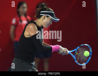 Hong Kong, China. 12th Oct, 2018. Garbine Muguruza of Spain hits a return during the singles quarterfinal match against Luksika Kumkhum of Thailand at 2018 Hong Kong Tennis Open in Hong Kong, China, Oct. 12, 2018. Garbine Muguruza won 2-0. Credit: Lo Ping Fai/Xinhua/Alamy Live News - Stock Photo