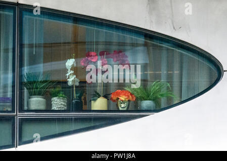 10-2018 Manhattan, New York.  Detail of Zaha Hadid's first New York condominium at 520 West 28th Street. Flowers in odd shaped window. Photo: © Simon - Stock Photo