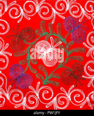 White, green and purple patterns on textiles of red color - Stock Photo