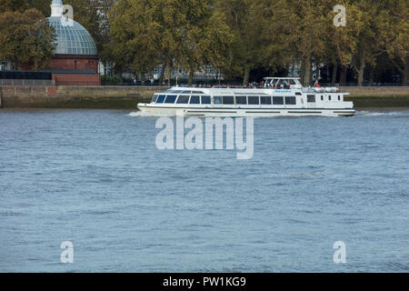 View from Greenwich, London, UK, to the entrance of the foot tunnel on the Canary Wharf side, with a tourist cruise boat passing on the river Thames. - Stock Photo