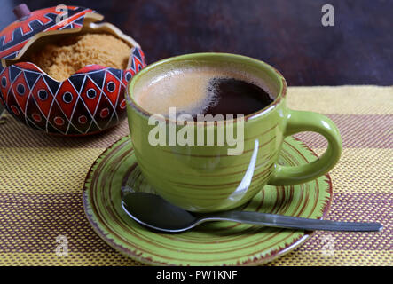 Hot coffee in a green cup with blurred sugar pot of brown sugar in backdrop served on stripe tablecloth - Stock Photo