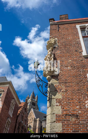 A sculpture of Mary holding baby Jesus on the top of a brick wall in Bruges, belgium Overlooking the St. Salvator's Cathedral - Stock Photo