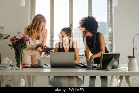 Group of young businesswomen working together in office. Females in casuals using digital tablet and laptop in modern office. - Stock Photo
