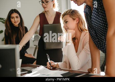 Group of young businesswomen in casuals looking at laptop and discussing work. Multi-ethnic female coworkers working together in office. - Stock Photo